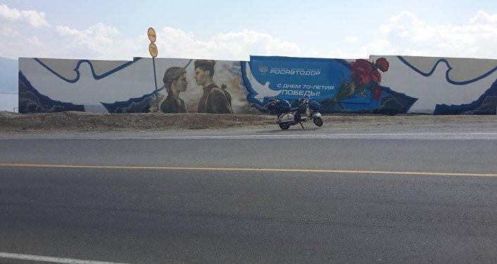 La vespa di Stefano Medvedich pargheggiata di fronte a un murales celebrativo del 70° anniversario della Vittoria