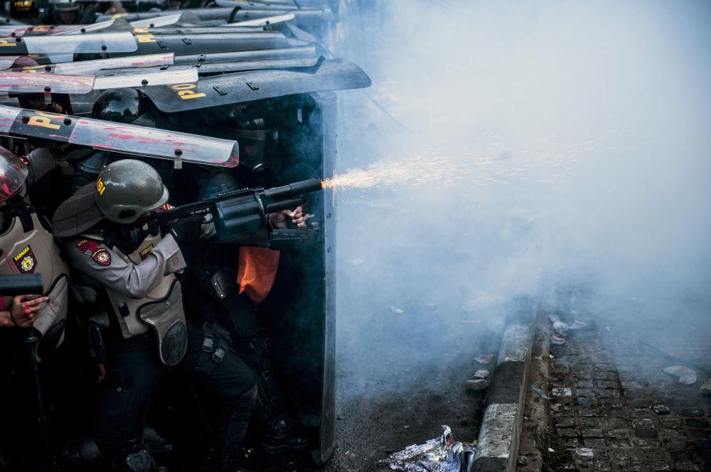 Un'agente di polizia usa gas lacrimogeno durante uno scontro con degli studenti manifestanti a Bandung, in Indonesia.