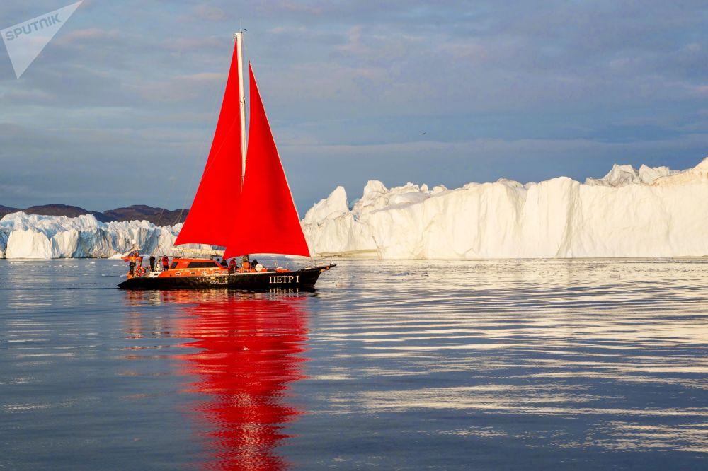 Lo yacht 'Pietro il Grande' naviga vicino ad un iceberg tra le acque dell'isola della Groenlandia durante la spedizione della società russa Rusark