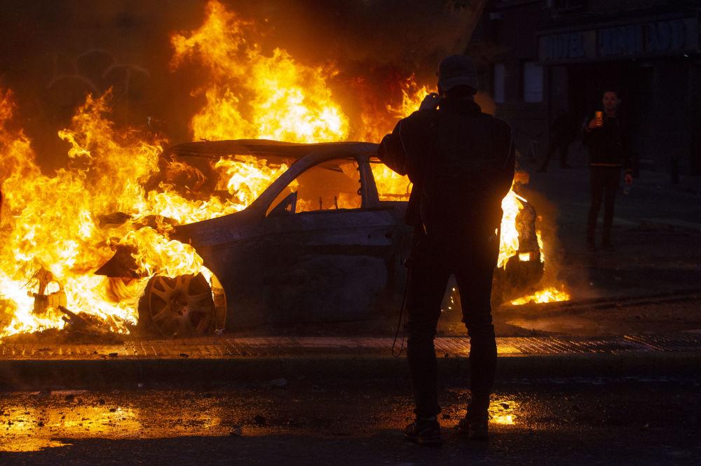 L'uomo scatta le foto di un'auto in fiamme durante le violente proteste a Santiago, il 19 ottobre 2019.