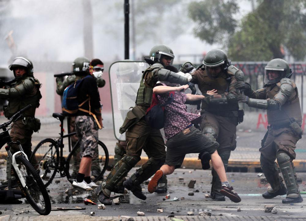 La polizia blocca un manifestante durante le proteste in Piazza Italia a Santiago il 23 ottobre 2019, Cile
