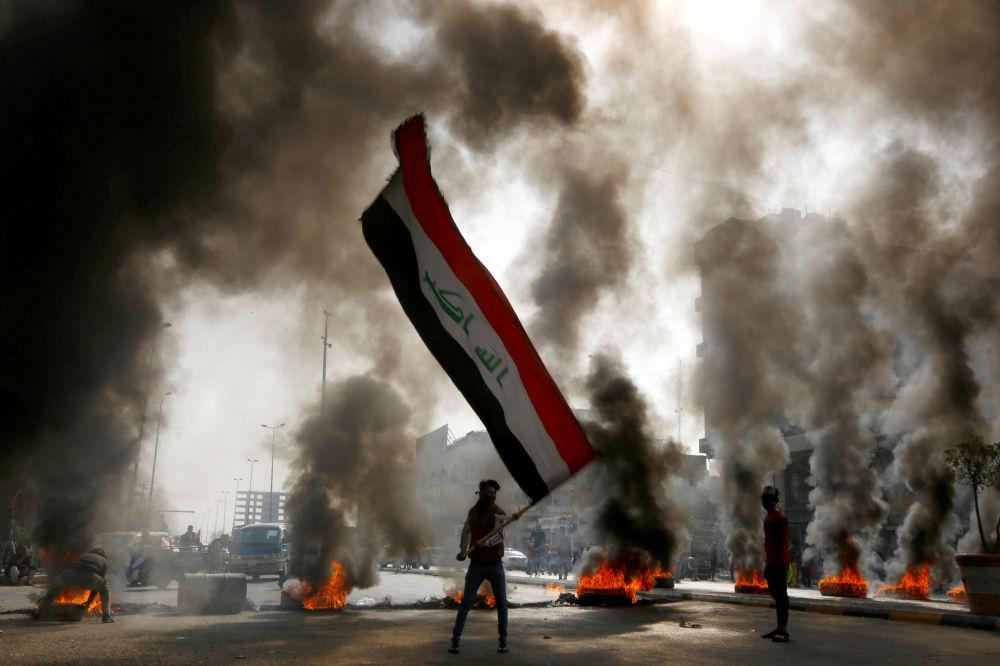 Un manifestante con la bandiera irachena durante le proteste a Najaf.