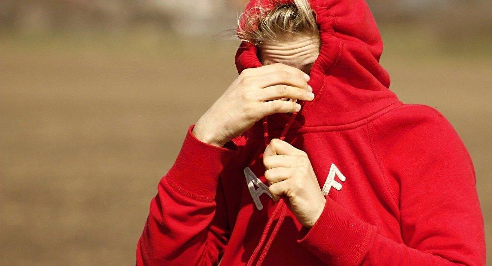 Una donna si copre il viso con la felpa