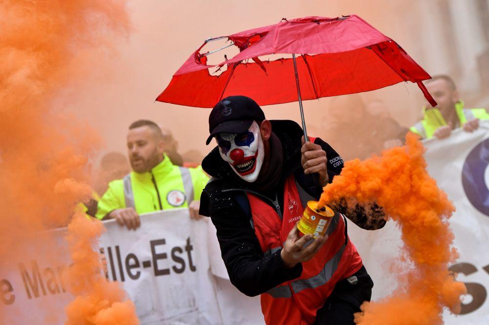 Un uomo con una maschera da clown ad una manifestazione contro la riforma delle pensioni a Marsiglia, in Francia.