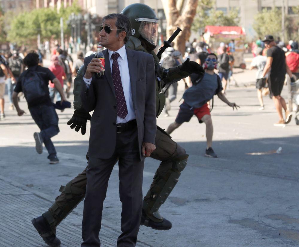 Un uomo beve la coca cola durante le proteste a Santiago del Cile.