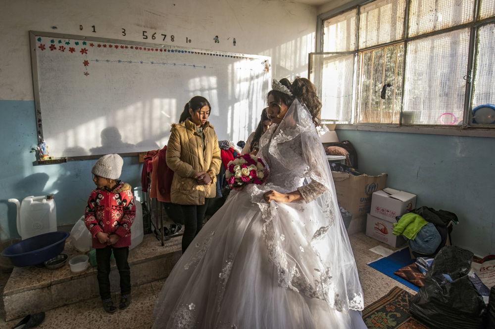 Una donna nel giorno di matrimonio in una scuola riattrezzata per l'alloggio temporaneo nella città Al-Hasakah, in Siria.