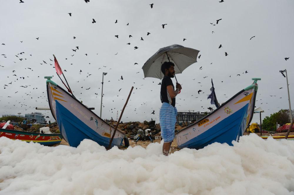 Un uomo su una spiaggia coperta da schiuma tossica in India.