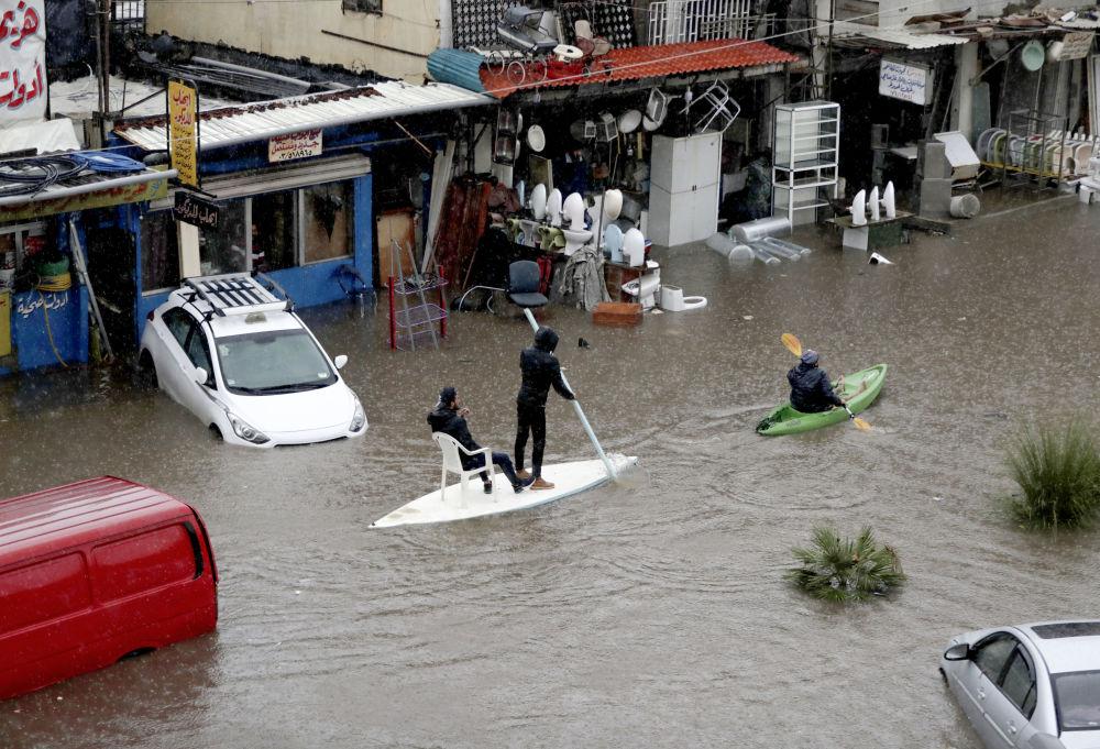 Cittadini libanesi usano una tavola da surf come mezzo di trasporto per una strada allagata a causa delle forti pioggi a Beirut, il 9 dicembre 2019