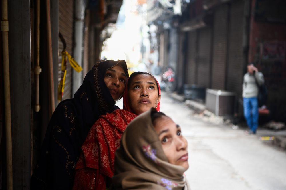 Le donne guardano la fabbrica in cui un giorno prima è scoppiato un incendio, nell'area di Anaj Mandi a Nuova Delhi, il 9 dicembre 2019