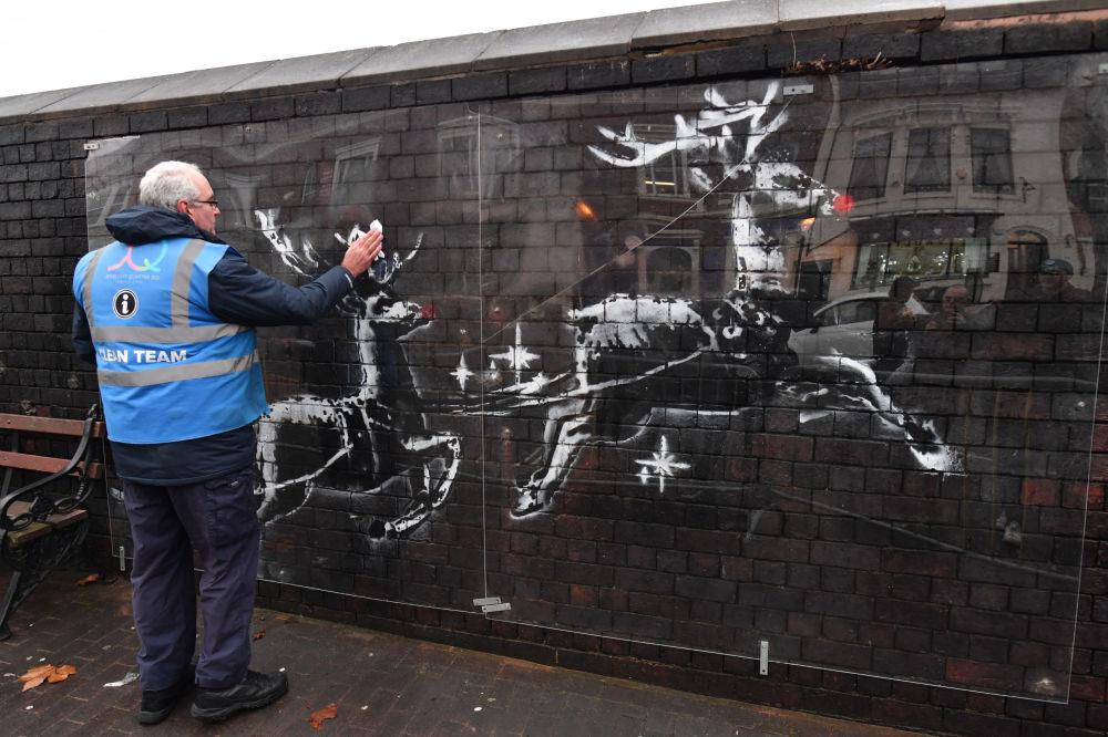 Un addetto pulisce un'opera d'arte dell'artista britannico Banksy, Birmingham, il 10 dicembre 2019