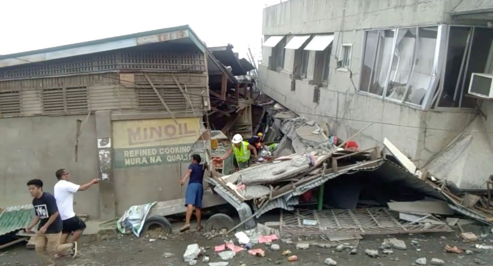 Rescue crew members look for trapped victims at collapsed building at Padada market, in Padada Philippines December 15, 2019 in this still image obtained from social media video. VINCENT YAJ MAKIPUTIN/via REUTERS THIS IMAGE HAS BEEN SUPPLIED BY A THIRD PARTY. MANDATORY CREDIT. NO RESALES. NO ARCHIVES.