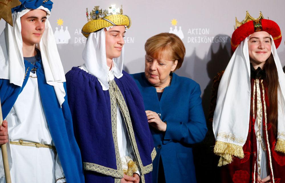 La cancelliera tedesca Angela Merkel con i cantanti durante un ricevimento presso la cancelleria tedesca a Berlino, Germania, il 7 gennaio 2020