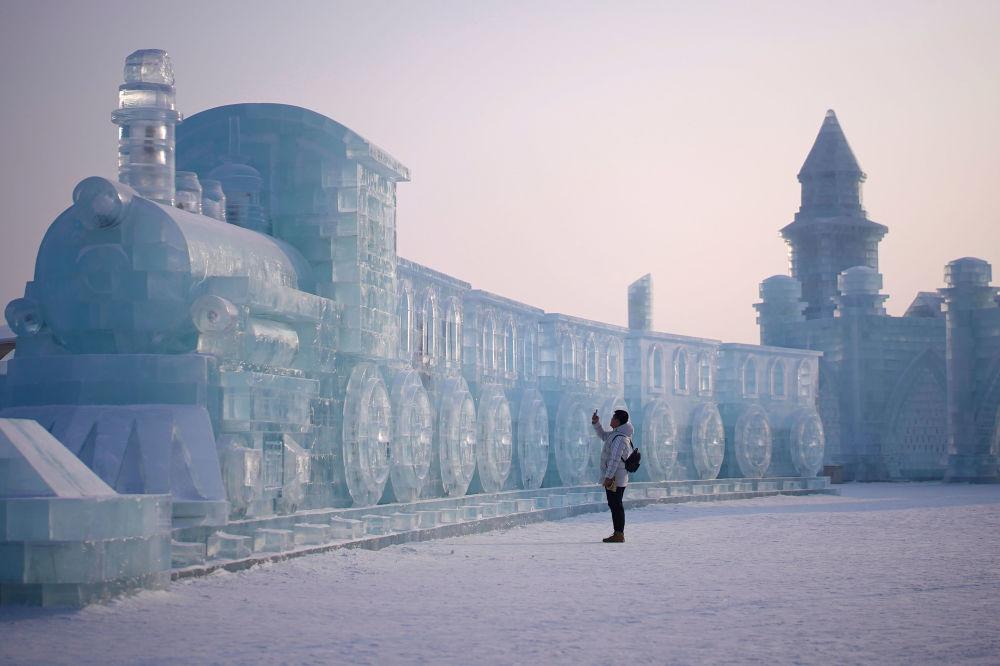 Un uomo accanto ad una scultura di ghiaccio a Harbin, Cina