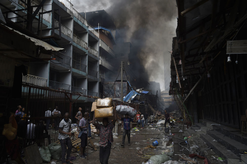 Ambulanti portano in salvo la merce durante un incendio in un mercato di Lagos, in Nigeria.