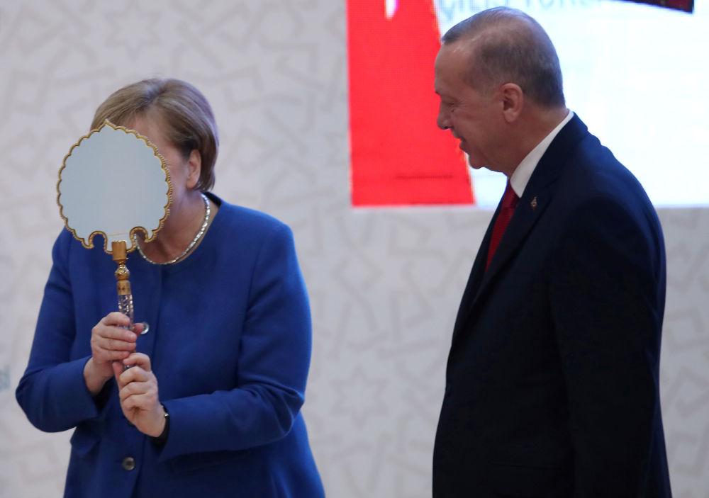 Il cancelliere tedesco Angela Merkel riceve un regalo dal presidente turco Recep Tayyip Erdogan.