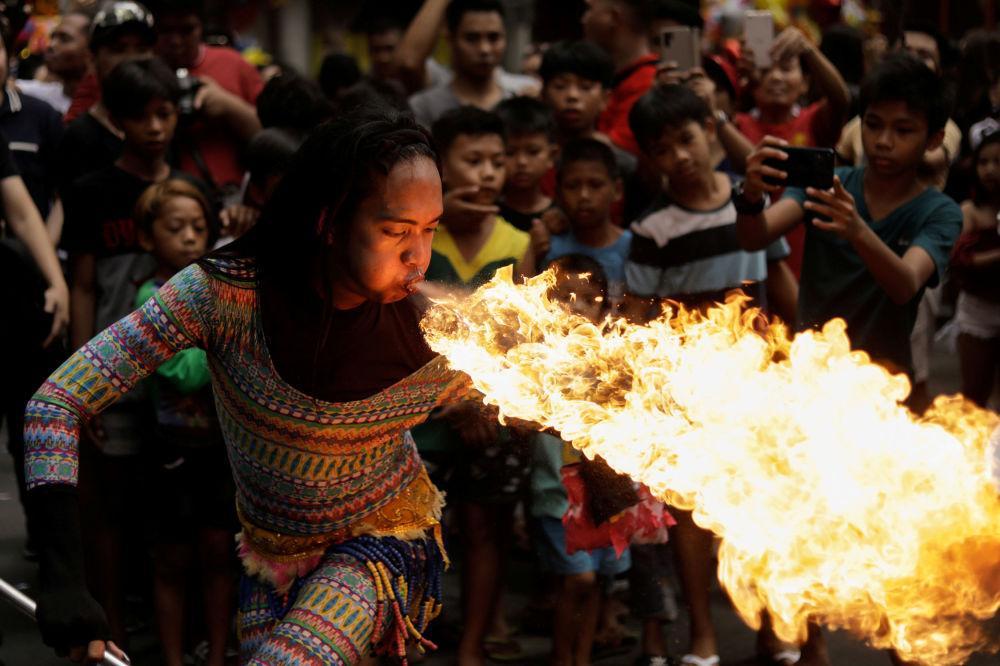 Un'artista di strada soffia fuoco dalla bocca alle celebrazioni del capodanno cinese a Manila, in Filippine.