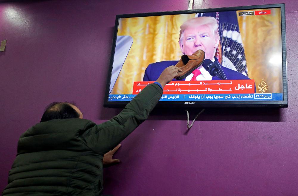 Un palestinese mette uno stivale sullo schermo del televisore in un caffè di Hebron (Al Khalil) dal quale Donald Trump parla del suo piano per un accordo in Medio Oriente.