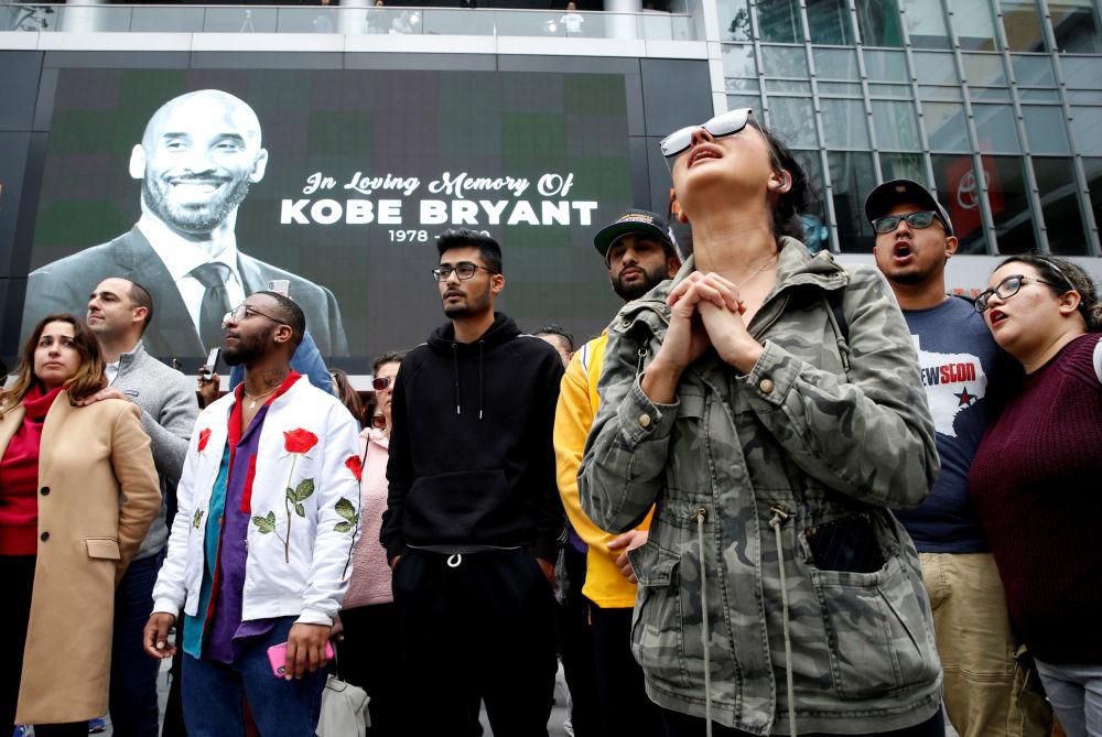 Persone in lutto vicino all'immagine del giocatore di basket Kobe Bryant a Los Angeles deceduto a seguito dell'incidente in un elicottero privato a Calabasas, in California.