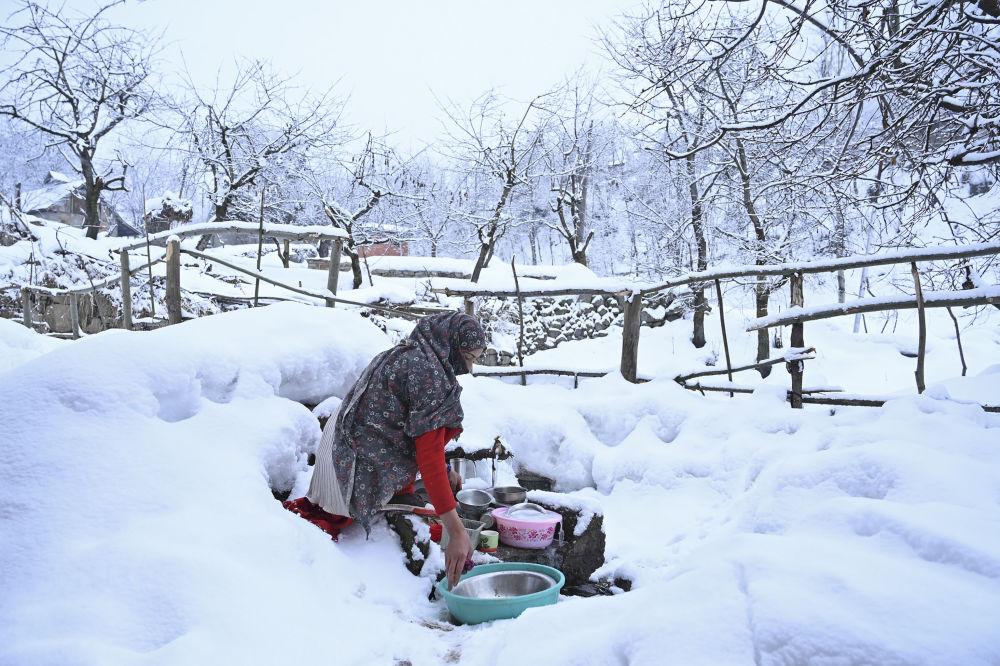 Donna lava i piatti a Srinagar, in India, dopo una nevicata