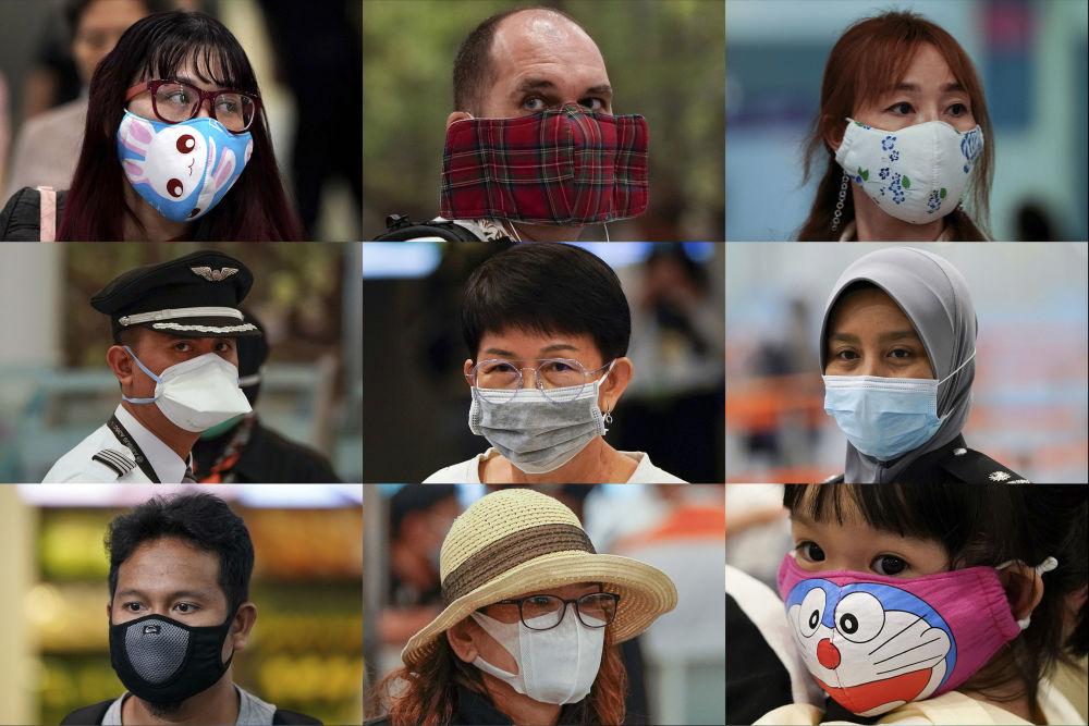 La gente indossa mascherine svariate all'ufficio immigrazioni all'aeroporto della città di Sepang, Malaysia