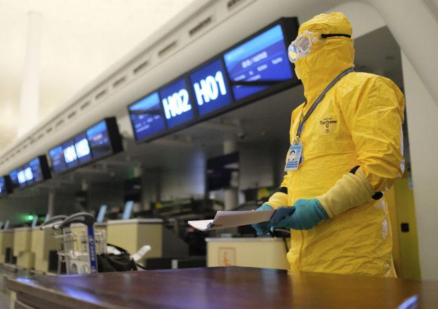 Un dipendente indossa un costume protettivo a Wuhan, Cina