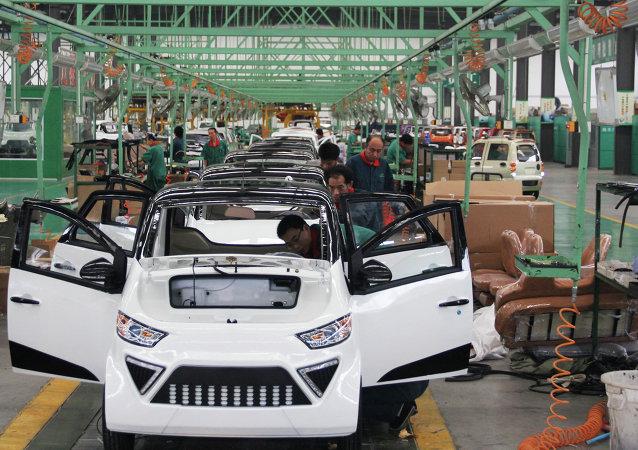 I lavoratori assemblano auto elettriche in una fabbrica di Zouping, nella provincia di Shandong, nella Cina orientale, il 16 settembre 2014